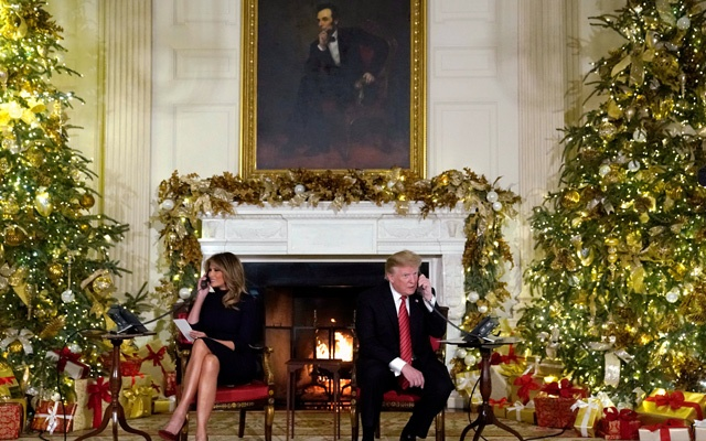 US President Donald Trump and first lady Melania Trump participate in NORAD Santa tracker phone calls from the White House in Washington, U.S. December 24, 2018. REUTERS/Jonathan Ernst