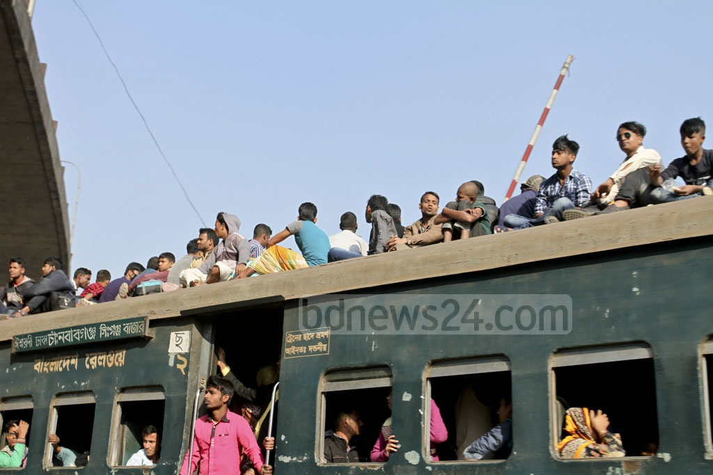 People sit on the roof of a train on Friday, risking their lives to cast their vote in the upcoming election. Photo: Asif Mahmud Ove