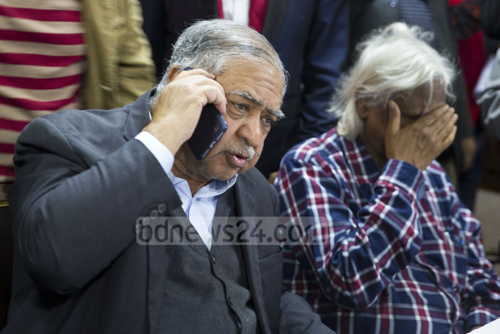 Jatiya Oikya Front chief Kamal Hossain speaks on the phone during a press conference midway through the 11th national parliamentary election on Sunday afternoon. Zafrullah Chowdhury sits next to him, looking distressed. Photo: Mostafigur Rahman