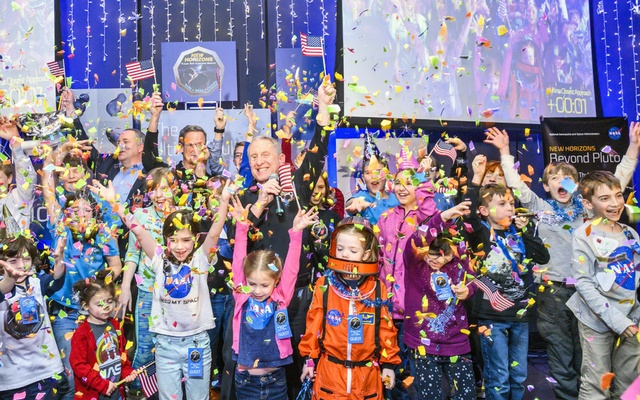 S. Alan Stern, center, New Horizons' principal investigator, is surrounded by children at Johns Hopkins University Applied Physics Laboratory in Laurel, Md., shortly after midnight on Tuesday morning, Jan. 1, 2019. They were celebrating the moment the NASA spacecraft New Horizons encountered Ultima Thule, an object orbiting one billion miles beyond Pluto. (Matt Roth/The New York Times)