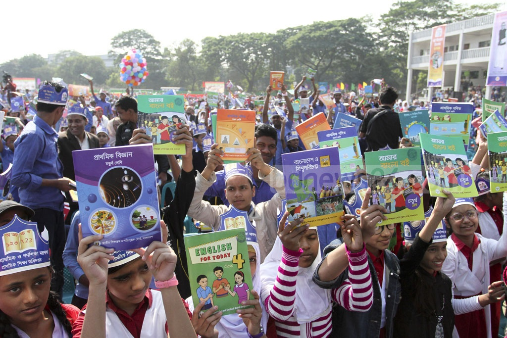 Students show off the new textbooks they received on Tuesday, the first day of the new year at the Dhaka University sports field. Photo: Asif Mahmud Ove