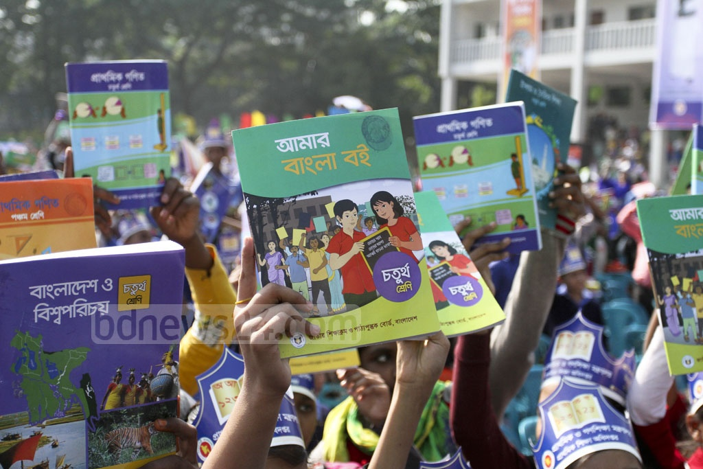 Happy students show off the new textbooks they received on Tuesday, the first day of the new year. Photo: Asif Mahmud Ove