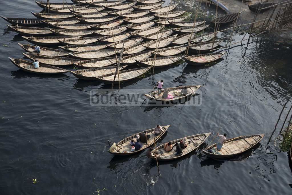 A row of boats floats above the tar-black waters of the Buriganga River in the Babubazar area. Photo: Mostafigur Rahman
