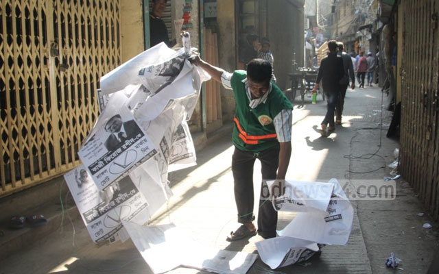 Workers clean up election campaign materials in the Suritola area of Old Dhaka on Wednesday. Photo: Asif Mahmud Ove