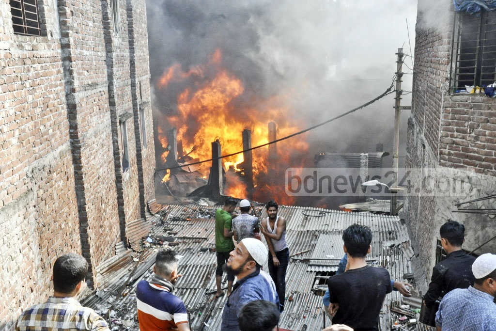 Locals along with the fire crews trying to douse a fire at some small plastic goods factories and warehouses at Lalbagh in Dhaka on Thursday.