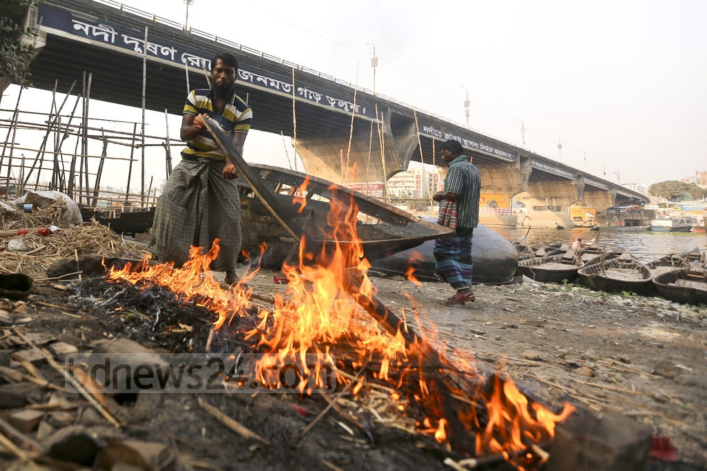 A boat is about to get some new wooden planks. A worker uses heat from a fire to bend the planks into shape. Photo: Mahmud Zaman Ovi