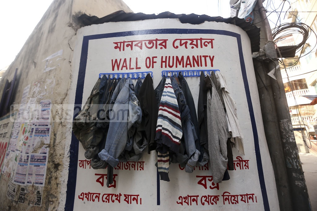 Local youths put together a 'wall of humanity' at the entrance of Sobhanbagh Government Officers Quarter. Anyone can leave their spare garments on the wall to be picked up by the needy. Photo: Mahmud Zaman Ovi