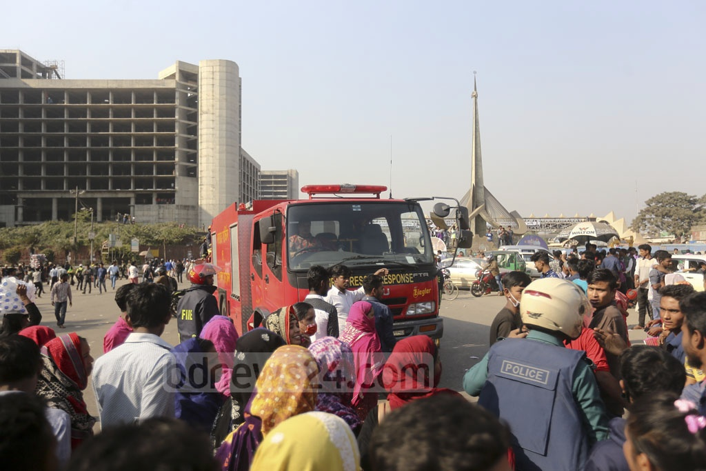Agitating workers block firefighters from reaching a bus they torched during a 5-hour blockade of Dhaka's Airport Road on Monday. Photo: Mahmud Zaman Ovi