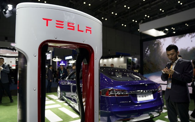 FILE PHOTO: A Tesla sign is seen during the China International Import Expo (CIIE), at the National Exhibition and Convention Center in Shanghai, China Nov 6, 2018. REUTERS/Aly Song/File Photo
