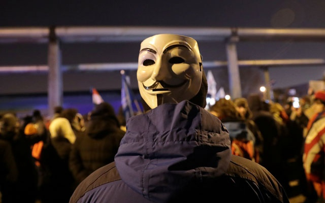 A demonstrator wears a Guy Fawkes mask during a protest against a proposed new labor law, billed as the