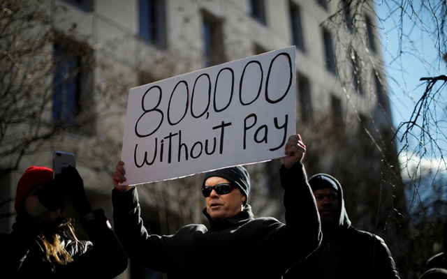 "FILE PHOTO: A demonstrator holds a sign, signifying hundreds of thousands of federal employees who won't be receiving their paychecks as a result of the partial government shutdown, during a ""Rally to End the Shutdown"" in Washington, US, Jan 10, 2019. REUTERS/Carlos Barria - RC112FDE54D0/File Photo"