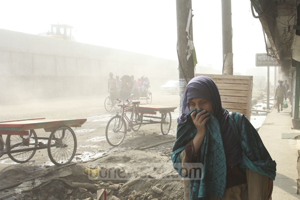 Pedestrians have to cover their faces when walking amid the dust-filled air Postogola. Photo: Asif Mahmud Ove