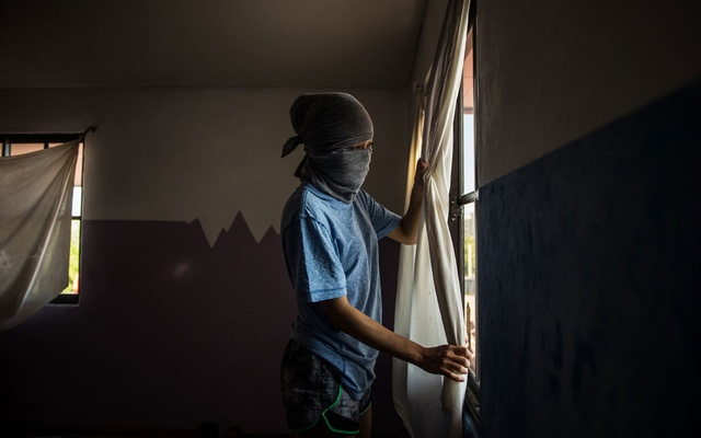 A dissident wanted by the Nicaraguan government looks out the window of a safe house, Dec 19, 2018. The New York Times