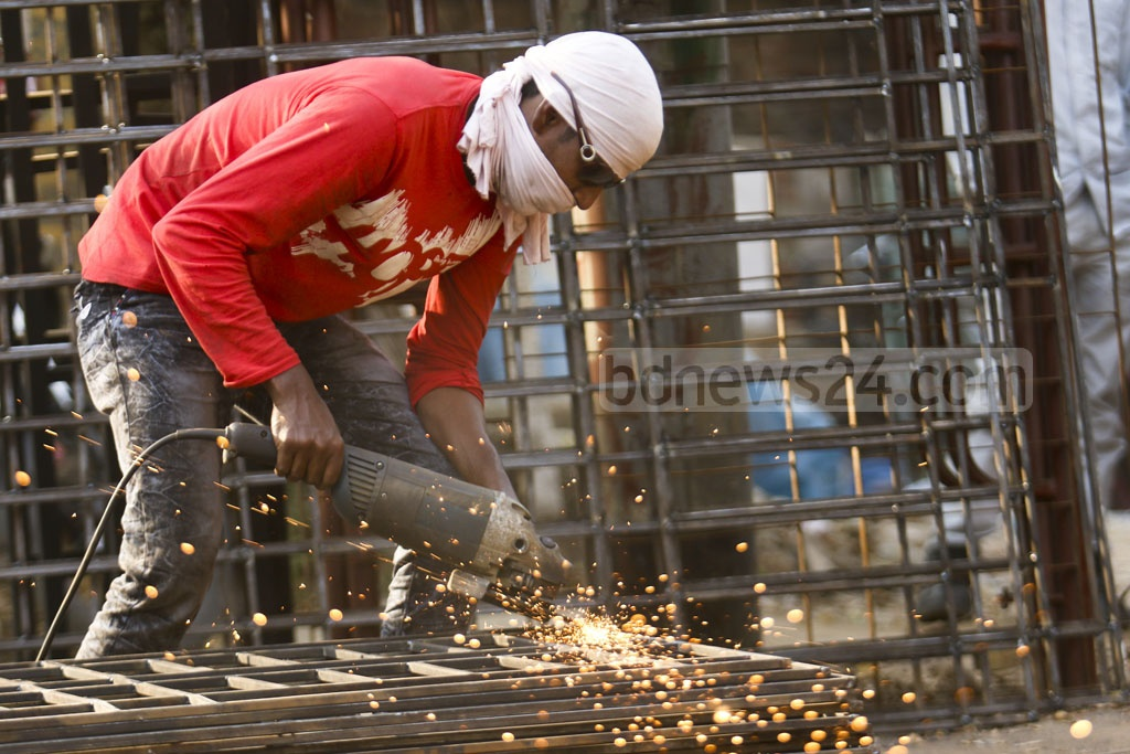A labourer welds iron grilles at Dhaka's Mogbazar without any safety equipment. Photo: Mahmud Zaman Ovi