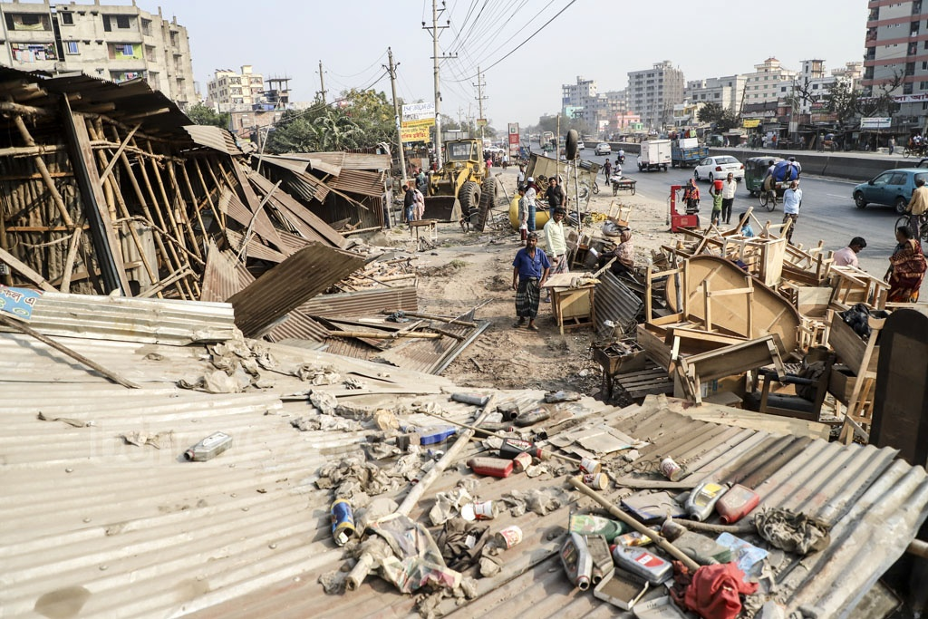 Workers of the Roads and Highways Department razing down an illegal structure during an eviction drive on the Dhaka-Chattogram Highway at Shanir Akhra on Monday. Photo: Abdullah Al Momin