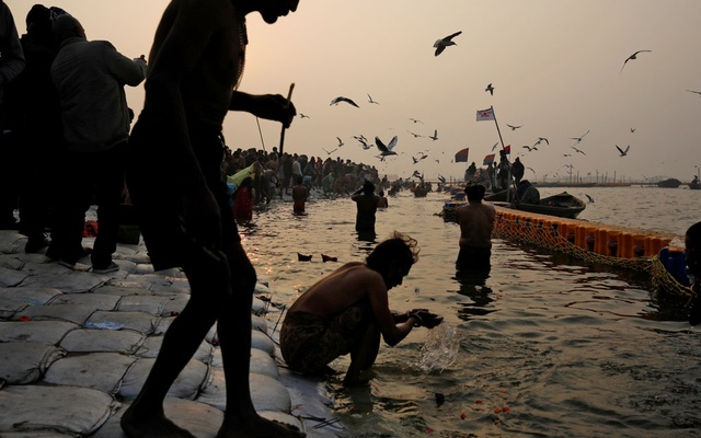 Devotees take a holy dip at Sangam, the confluence of the Ganges, Yamuna and Saraswati rivers, during