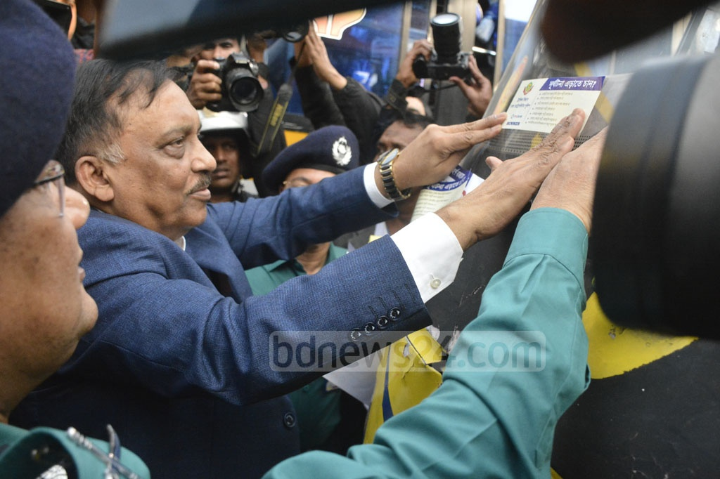 Home Minister Asaduzzaman Khan putting traffic awareness stickers on vehicles after inaugurating a fortnightly campaign programme at at Zero Point in Dhaka's Gulistan on Tuesday.