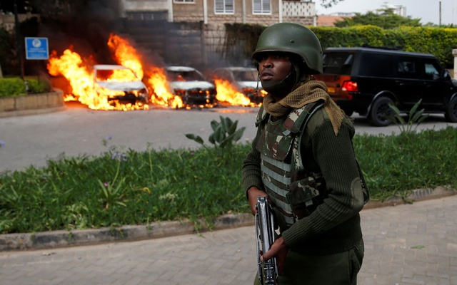A member of security forces walks as cars are seen on fire at the scene where explosions and gunshots were heard at the Dusit hotel compound, in Nairobi, Kenya January 15, 2019. Reuters