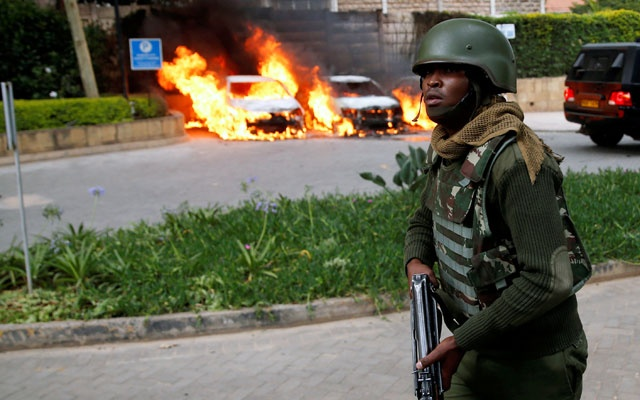 A policeman runs past burning cars at the scene where explosions and gunshots were heard at the Dusit hotel compound, in Nairobi, Kenya Jan 15, 2019. REUTERS