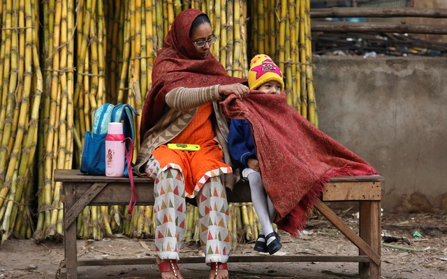 A mother covers her daughter with a stole to keep her warm as they wait for a school bus on a cold winter morning in Kolkata, India, January 18, 2019. REUTERS/Rupak De Chowdhuri