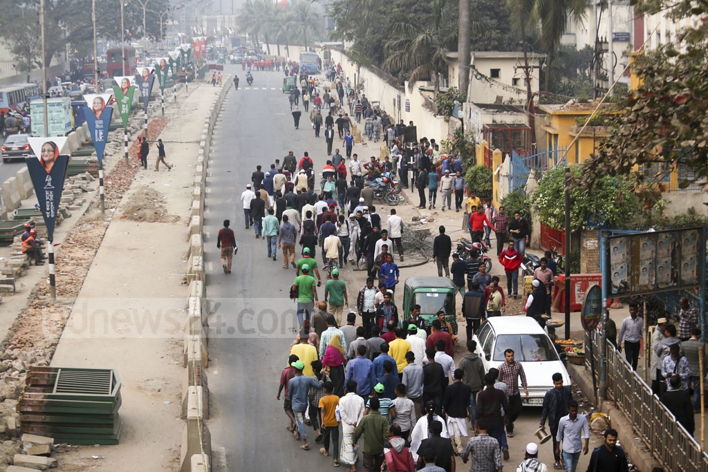People walk to their destinations as vehicles remain stuck in tailbacks caused by traffic restrictions during the Awami League's election victory celebration at the Suhrawardy Udyan in Dhaka.