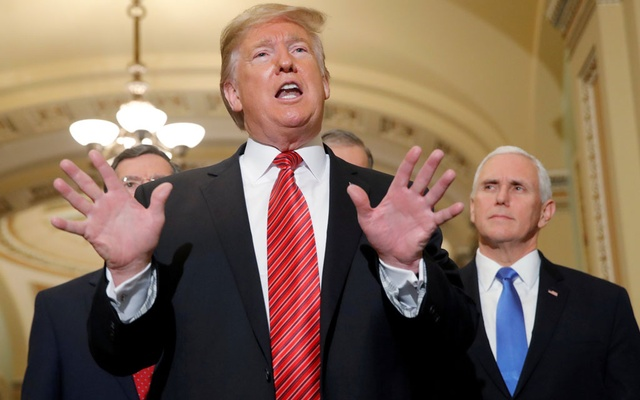 FILE PHOTO: US President Donald Trump talks to reporters as Vice President Mike Pence looks on as the president departs after addressing a closed Senate Republican policy lunch while a partial government shutdown enters its 19th day on Capitol Hill in Washington, US, Jan 9, 2019. REUTERS/Jim Young/File Photo