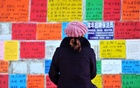 A woman looks at job advertisements on a wall in Qingdao West Coast New Zone in Shandong province, China Jan 17, 2019. REUTERS