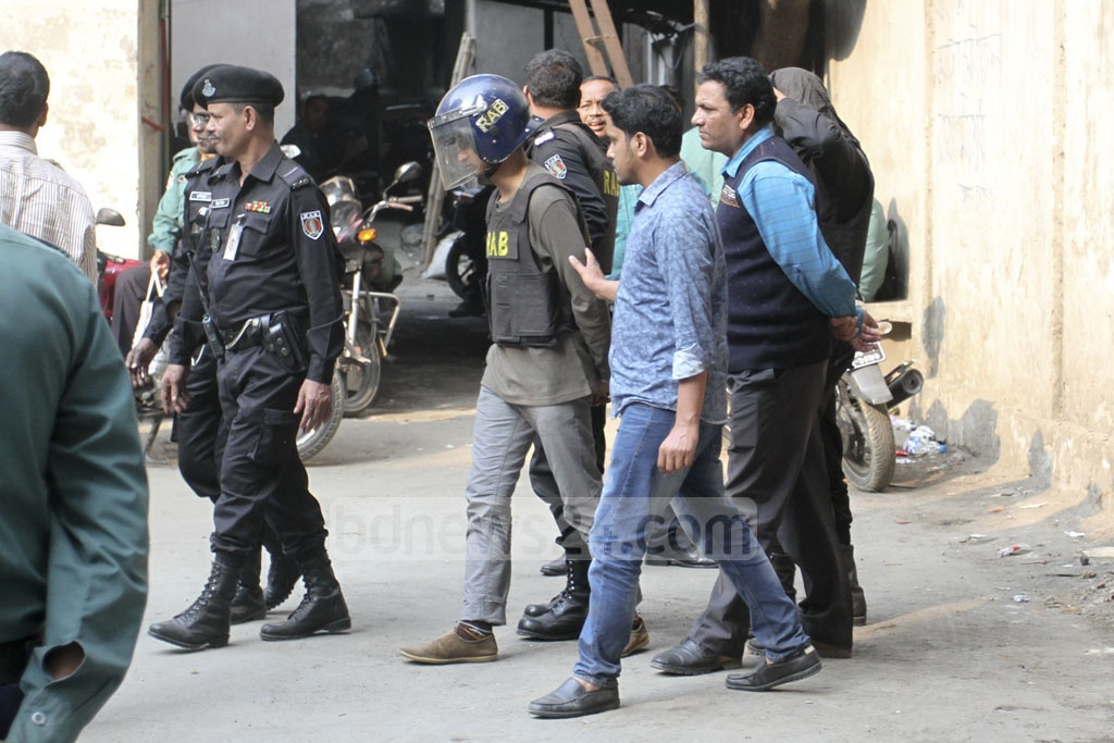 RAB personnel escorting Mamunur Rashid Ripon, a suspected militant who was a fugitive in the case over the 2016 Gulshan cafe attack, to Dhaka's CMM Court on Sunday. RAB arrested him in Gazipur on Saturday midnight. Photo: Asif Mahmud Ove