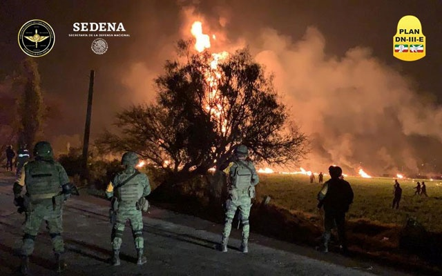 Military personnel watch as flames engulf an area after a ruptured fuel pipeline exploded, in the municipality of Tlahuelilpan, Hidalgo, Mexico, near the Tula refinery of state oil firm Petroleos Mexicanos (Pemex), Jan 18, 2019 in this handout photo provided by the National Defence Secretary (SEDENA). National Defence Secretary/Handout via REUTERS
