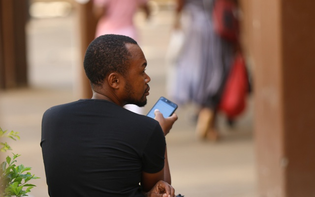 FILE PHOTO: A man checks his mobile phone in Harare, Zimbabwe, January 18, 2019. Reuters