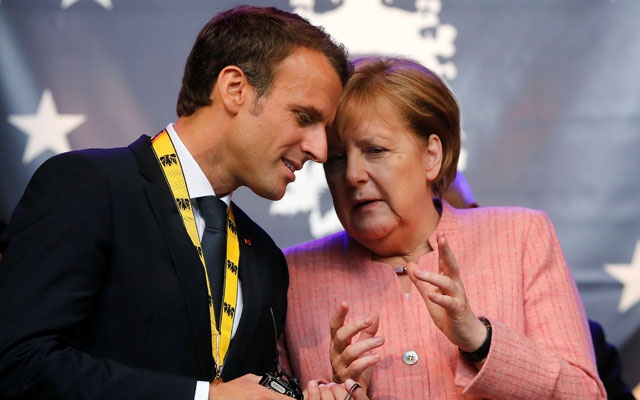 French President Emmanuel Macron speaks with German Chancellor Angela Merkel after being awarded the Charlemagne Prize for