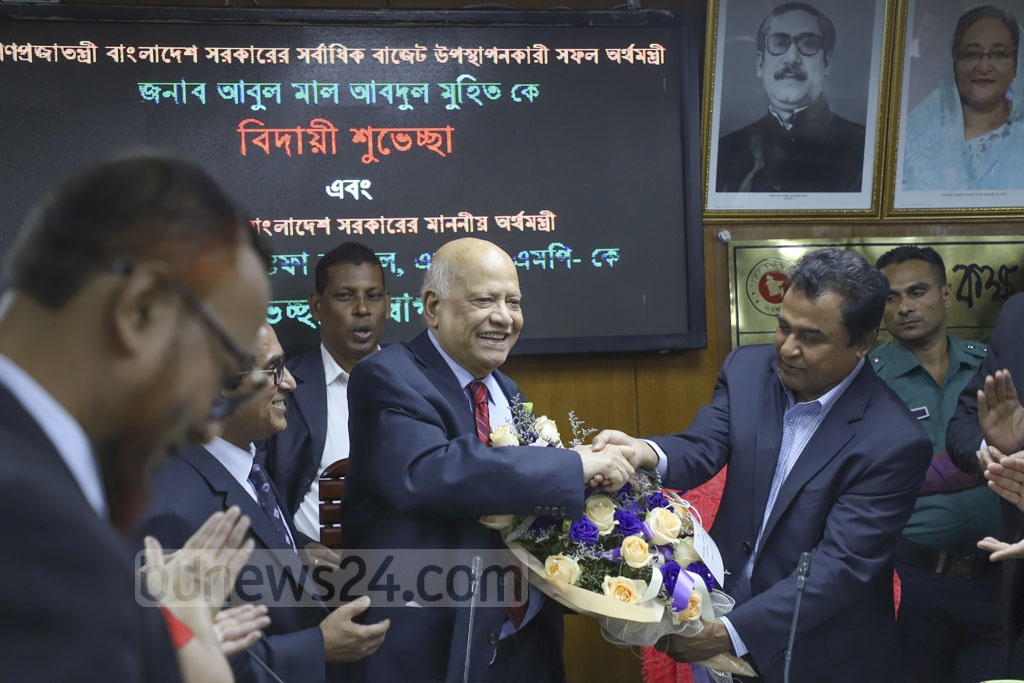 Finance Minister AHM Mustafa Kamal greets former Finance Minister Abul Maal Abdul Muhith with a bouquet on Thursday at a ceremony at the National Board of Revenue. Photo: Abdullah Al Momin