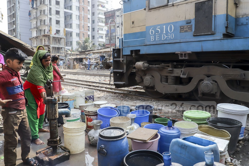 People place their lives at risk by collecting water from the pump right next to the railway track. Photo: Abdullah Al Momin