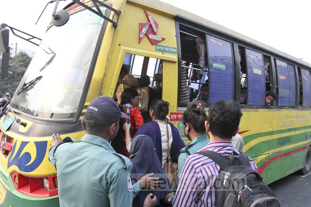 Traffic police helps a visually impaired woman catch a bus from Banani's Kakoli intersection on Sunday. Photo: Asif Mahmud Ove