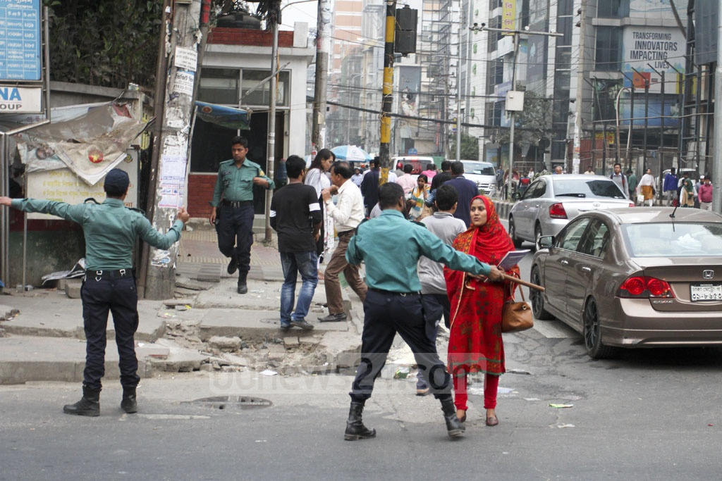Police stop jaywalkers at Banani's Kakoli intersection and get them to use a nearby foot-over bridge on Sunday. Photo: Asif Mahmud Ove