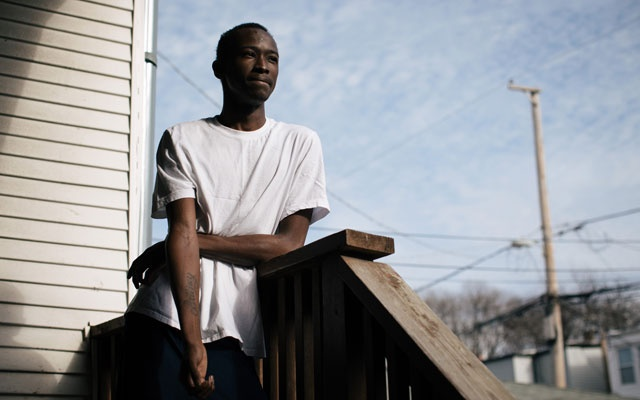 Brandon Williams, whose sister died in 2015 from complications with sickle-cell disease, stands on his family's back porch, in Chicago, Dec 19, 2018. The New York Times