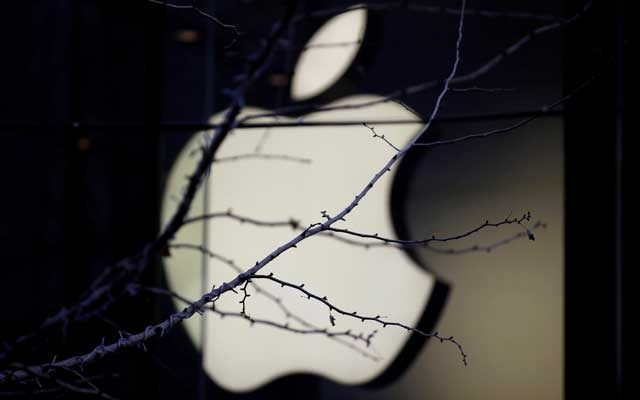 An Apple company logo is seen behind tree branches outside an Apple store in Beijing, China Dec 14, 2018. REUTERS