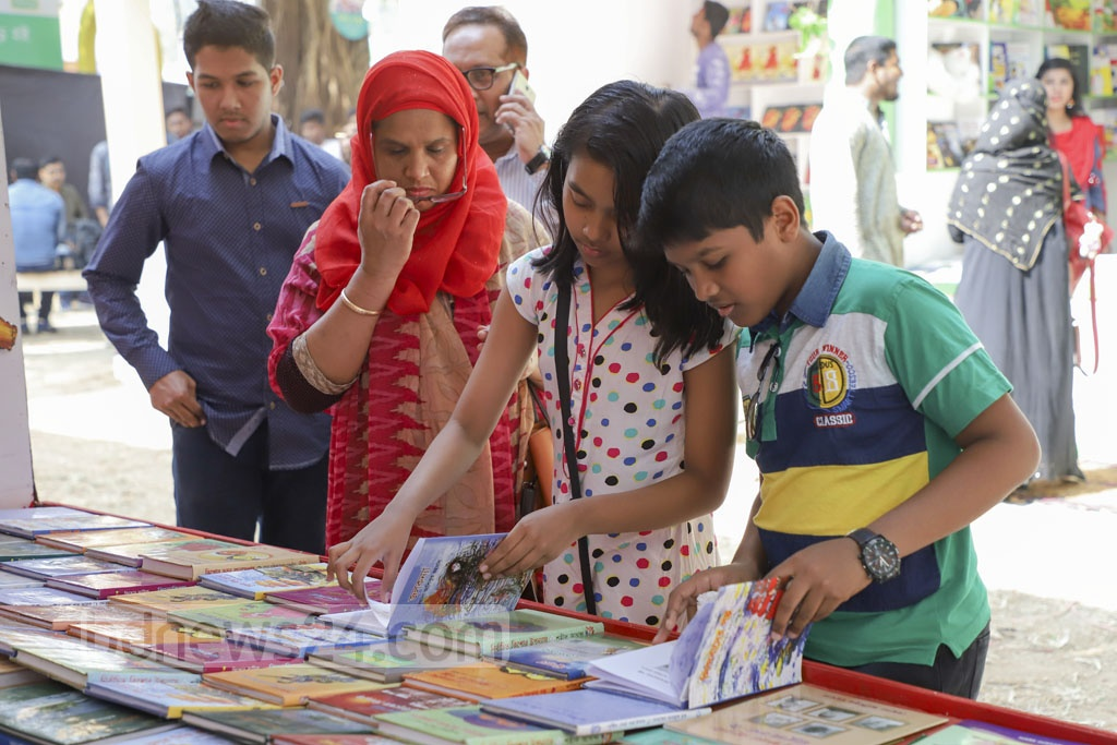 A tiny tot checks the content of a book during the first Children's Hour at the month-long Ekushey Book Fair on Saturday. The hours between 11:00 am and 1:00 pm on Fridays and Saturdays have been reserved especially for kids. Photo: Abdullah Al Momin