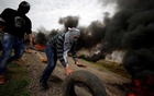 A Palestinian demonstrator rolls a tire during clashes with Israeli forces at a protest in al-Mughayer village near Ramallah, in the Israeli-occupied West Bank, Feb 1, 2019. REUTERS