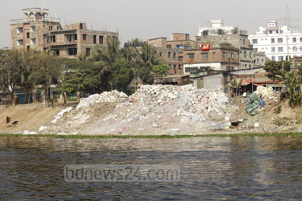 Plastic grindings dumped on the bank of the Buriganga River in Dhaka for recycling are being washed away, mixed in the already polluted water. Photo: Mahmud Zaman Ovi
