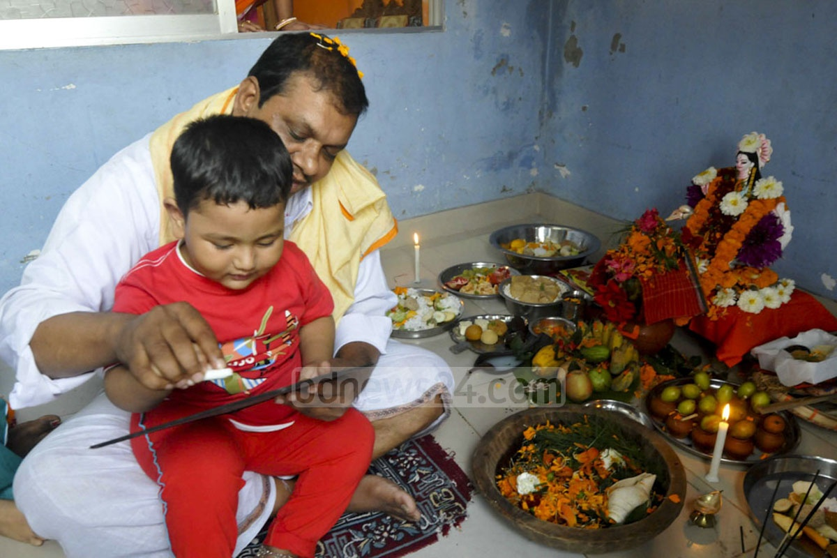 A child is introduced to the Bangla alphabet as part of a Saraswati Puja ceremony in Old Dhaka.