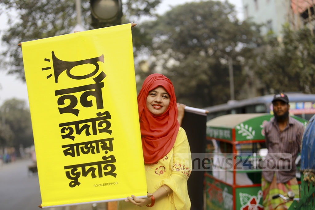 Mominur Rahman Royal has been raising awareness on noise pollution among drivers on his own initiative for four years. The noise levels created by drivers' honking on Dhaka's roads exceed 80 decibels and can damage hearing, he says. An activist holds a banner with Royal's slogan against honking which has gained popularity on social media. Photo: Mahmud Zaman Ovi