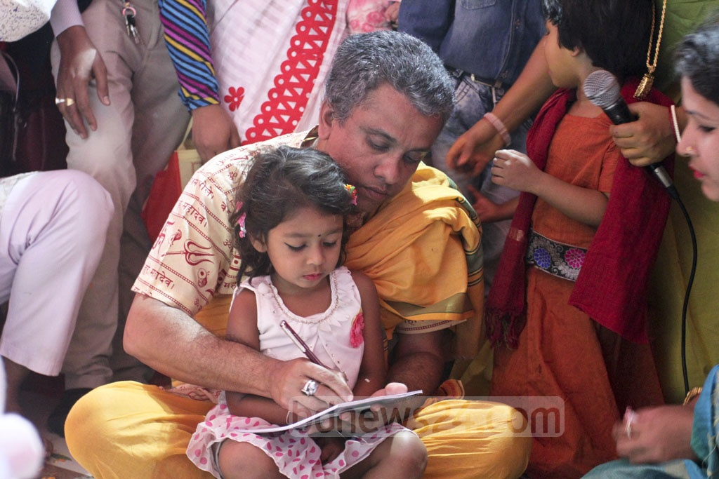 Hindu priests present children with writing materials while reading mantras during the Saraswati Puja. They begin their official schooling through their introduction to the alphabet. The practice is known as Hatekhori. Photo: Asif Mahmud Ove