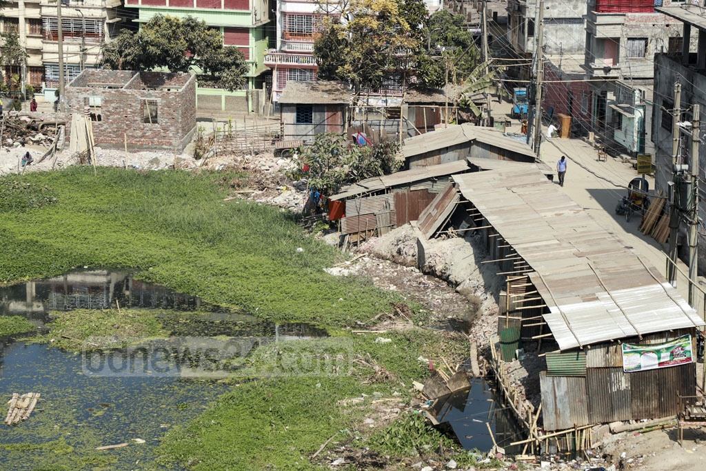 Rickshaw garages, shops, offices of different political groups have been built illegally on the verges of the DIT pond next to Satish Sarker Road in the capital's Gandaria. The years-old water body will cease to exist if proper steps are not taken to stop encroachment. This photo was taken on Monday. Photo: Abdullah Al Momin