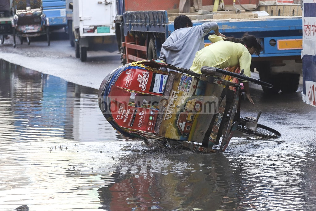 Metrorail project work has clogged sewerage system at Senpara in Dhaka's Mirpur, flooding Rokeya Sarani with dirty water and adding to sufferings of pedestrians and commuters. This photo was taken on Tuesday. Photo: Abdullah Al Momin