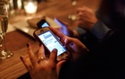 A smartphone user at a bar in Manhattan, Feb. 5, 2015. Americans looking for love lost at least $143 million to romance scammers in 2018. The New York Times