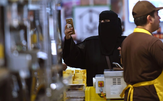 A Saudi woman uses her cell phone to take pictures of the International Coffee and Chocolate Exhibition. The New York Times