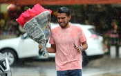 A man carries flowers in the rain in the flower district on Valentine's Day in Los Angeles, California, US, Feb 14, 2019. REUTERS