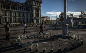 A man in Guatemala City stops on Oct 30, 2018, to look at a memorial to the victims and survivors of a fire at a youth shelter. The New York Times