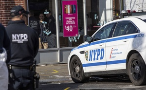 New York Police Department detectives examine bullet holes at a cellphone store where a fellow officer responding to an armed robbery was killed by friendly fire the night before, in Queens, Feb 13, 2019. Detective Brian Simonsen, a 19-year veteran, is the first NYPD officer killed in the line of duty since July 2017. The New York Times